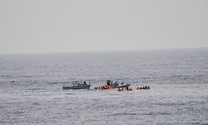 In this photo taken in the Mediterranean Sea, off the Libyan coast, Friday, May 27, 2016, rescuers help migrants to board rubber dinghies before towing them to the Vega.