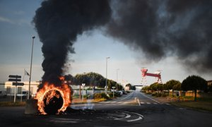 Striking workers set up a burning barricade to block access to the harbour of Saint-Nazaire in western France, on May 24, 2016, to protest against the government's planned labour law reforms.