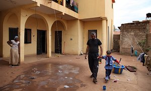 Cemal Ahmed, a 40-year-old refugee from the civil war in Syria, plays with his daughter at their apartment block in Bamako.