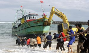Indonesian security personnel try to push a stranded Sri Lankan boat using a backhoe into the open sea, at Lhoknga beach in Indonesia on 20 June