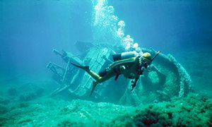 scuba diver with shipwreck underwater in Gozo Malta
