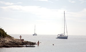Boats moored off Sveti Klement Island and a couple of swimmers, Croatia.