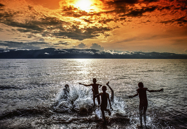 Children playing in the water of the Tanganyika Lake at sunset, Burundi, Africa