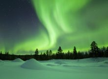 The Northern Lights over a snowy winter landscape in Finnish Lapland